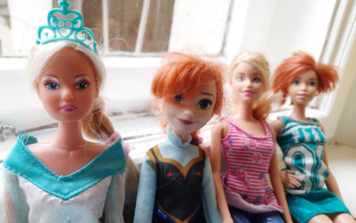 Vier Barbiepuppen, zwei sind blond, zwei rothaarig. Sie sitzen nebeneinander auf einer Fensterbank. Im Hintergrund ist das Fenster zu sehen.