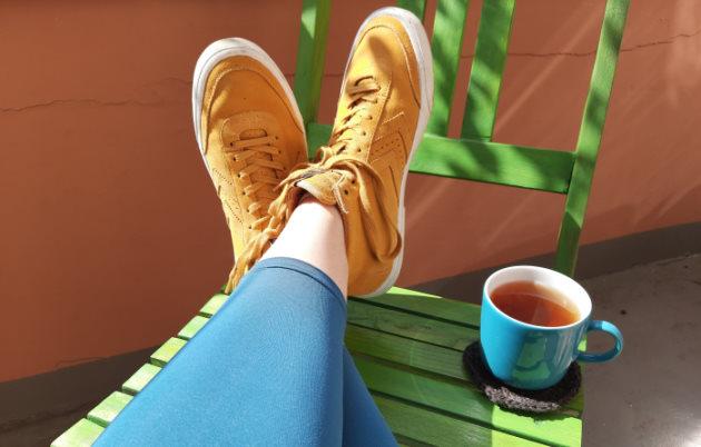 Zwei Beine mit petrolfarbenen Leggings liegen übereiander auf einem grünen Stuhl. Daneben auf dem Stuhl steht eine volle Teetasse.
